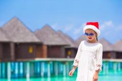 Pequeña muchacha adorable en el sombrero rojo de Papá Noel en blanco Foto de archivo