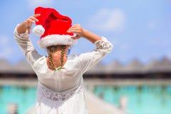 Pequeña muchacha adorable en el sombrero rojo de Papá Noel en blanco Imagenes de archivo
