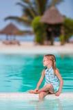 Pequeña muchacha adorable feliz al borde de la piscina al aire libre Fotos de archivo