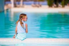 Pequeña muchacha adorable feliz en piscina al aire libre La muchacha hermosa del adolescente disfruta de vacaciones en el hotel e Fotos de archivo