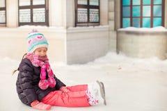 Pequeña muchacha adorable que se sienta en el hielo con los patines Imágenes de archivo libres de regalías