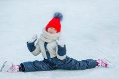Pequeña muchacha adorable que se sienta en el hielo con los patines después de caída Foto de archivo