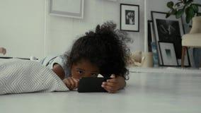 Pequeña muchacha afroamericana dulce que usa smartphone almacen de video
