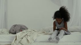 Pequeña muchacha afroamericana dulce que usa smartphone almacen de metraje de vídeo