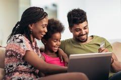 Pequeña muchacha afroamericana linda y sus padres jovenes hermosos que usan un ordenador portátil y haciendo compras en línea imágenes de archivo libres de regalías