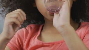 Pequeña muchacha afroamericana que bebe el agua clara del vidrio plástico, bebida almacen de metraje de vídeo