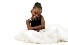 Pequeña muchacha afroamericana que sostiene una tableta digital Imagenes de archivo
