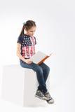 Pequeña muchacha alegre con el libro en el fondo blanco Fotografía de archivo libre de regalías