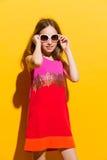Pequeña muchacha alegre de la moda que presenta con las gafas de sol Fotos de archivo