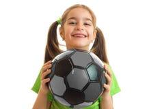 Pequeña muchacha alegre en jugar uniforme del verde con el balón de fútbol Foto de archivo