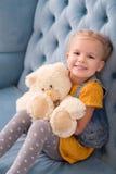 Pequeña muchacha alegre que sostiene un oso de peluche Foto de archivo