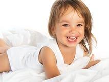 Pequeña muchacha alegre sonriente feliz en una cama aislada Foto de archivo