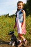 Pequeña muchacha americana linda con un su perro para un paseo Imagen de archivo