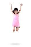 Pequeña muchacha asiática adorable y feliz que salta en aire imagen de archivo