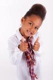 Pequeña muchacha asiática africana linda que hace los pulgares para arriba Imagenes de archivo