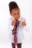 Pequeña muchacha asiática africana linda que hace los pulgares para arriba Imagen de archivo libre de regalías