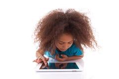 Pequeña muchacha asiática africana que usa una PC de la tablilla Imagen de archivo libre de regalías