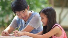 Pequeña muchacha asiática con el padre que hace la preparación almacen de video