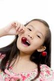 Pequeña muchacha asiática con la cereza roja fresca Fotos de archivo