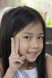 Pequeña muchacha asiática con la muestra de la mano de la victoria. Foto de archivo