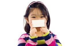 Pequeña muchacha asiática con la tarjeta de visita Fotos de archivo libres de regalías
