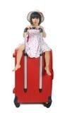 Pequeña muchacha asiática en un sombrero de la armadura que se sienta en un viaje enorme su rojo Fotos de archivo