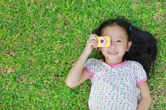 Pequeña muchacha asiática feliz del niño con la cámara digital que miente en fondo verde del césped fotografía de archivo libre de regalías