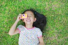 Pequeña muchacha asiática feliz del niño con la cámara digital que miente en fondo verde del césped fotos de archivo libres de regalías