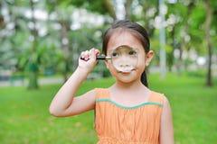 Pequeña muchacha asiática linda del niño que mira a través del vidrio magnifiying encendido la hierba al aire libre imágenes de archivo libres de regalías