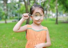 Pequeña muchacha asiática linda del niño que mira a través del vidrio magnifiying encendido la hierba al aire libre imagen de archivo