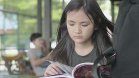 Pequeña muchacha asiática linda en la ropa casual que se sienta para gozar del libro de lectura en el café almacen de video