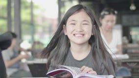 Pequeña muchacha asiática linda en la ropa casual que se sienta para gozar del libro de lectura en el café metrajes