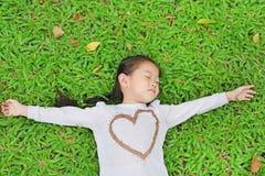 Pequeña muchacha asiática linda feliz del niño que miente en césped verde Sonriendo y cerrado la ojos imagen de archivo