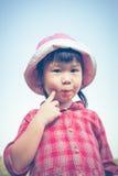 Pequeña muchacha asiática linda que come una piruleta en fondo de la naturaleza adentro Foto de archivo libre de regalías