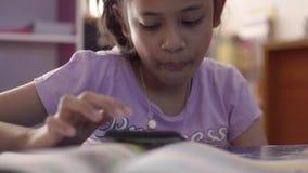 Pequeña muchacha asiática linda vídeo que usa y de observación del teléfono móvil en el escritorio del estudio metrajes