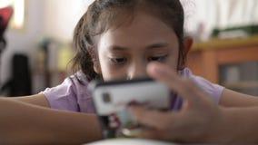 Pequeña muchacha asiática linda vídeo que usa y de observación del teléfono móvil en el escritorio del estudio almacen de video