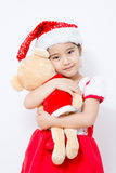 Pequeña muchacha asiática que abraza la muñeca del oso en la Navidad Fotos de archivo