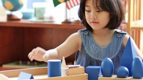Pequeña muchacha asiática que apila bloques del montessori almacen de video