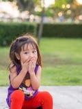 Pequeña muchacha asiática que cubre su boca con sus manos Fotos de archivo