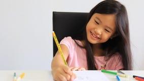 Pequeña muchacha asiática que dibuja una imagen en la tabla almacen de metraje de vídeo