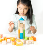 Pequeña muchacha asiática que juega bloques de madera coloridos Fotos de archivo