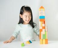 Pequeña muchacha asiática que juega bloques de madera coloridos Fotografía de archivo libre de regalías