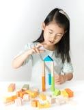 Pequeña muchacha asiática que juega bloques de madera coloridos Imagen de archivo