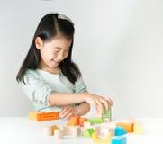Pequeña muchacha asiática que juega bloques de madera coloridos Imagenes de archivo