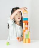 Pequeña muchacha asiática que juega bloques de madera coloridos Foto de archivo libre de regalías