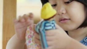 Pequeña muchacha asiática que juega con la muñeca almacen de video