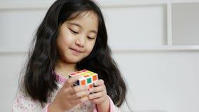 Pequeña muchacha asiática que juega el cubo del rubik en la cama almacen de video