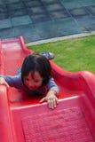 Pequeña muchacha asiática que juega en el resbalador Imagen de archivo