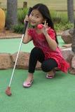 Pequeña muchacha asiática que juega a mini golf Fotos de archivo
