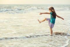 Pequeña muchacha asiática que juega y que se divierte en el mar en la puesta del sol fotografía de archivo